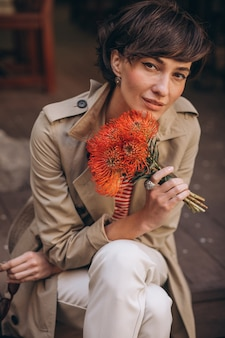 Young woman with flowers sitting in the street