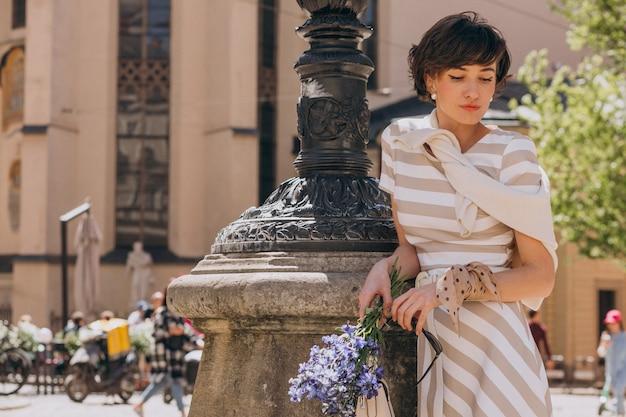 Молодая женщина с цветами гуляет по городу