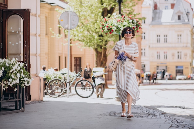 Young woman with flowers walking in town
