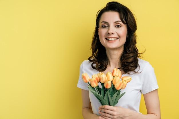 花を持つ若い女性