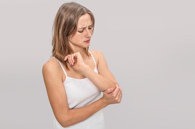 そばかすのある若い女性は、肘に手を握っています。痛みがあります。彼女は真剣です。若い女性は白いtシャツを着ています。