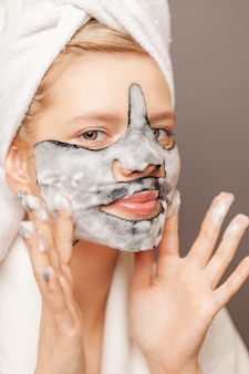 Young woman with fresh healthy skin and hairs aplying alginate mask and smiling