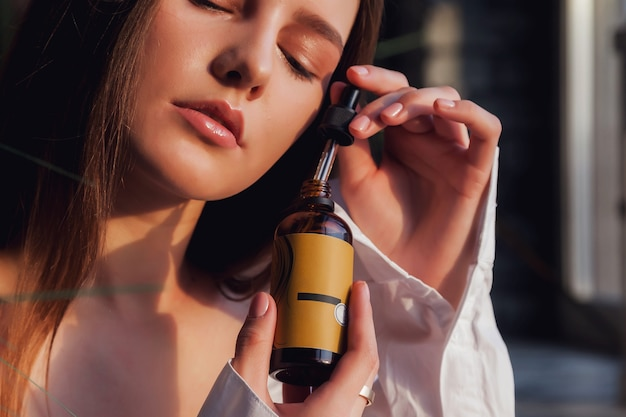 オイルでバスルームの室内の風呂でポーズをとって新鮮な完璧な肌を持つ若い女性。美容と治療の概念。健康的なライフスタイル、spa、セルフケアの広告コンセプト。コピースペース