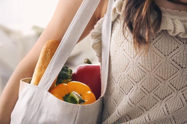 エコバッグ、クローズアップで新鮮な製品を持つ若い女性