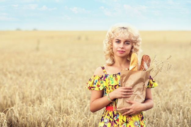 Young woman with a full pack of bread in a field with ripe wheat