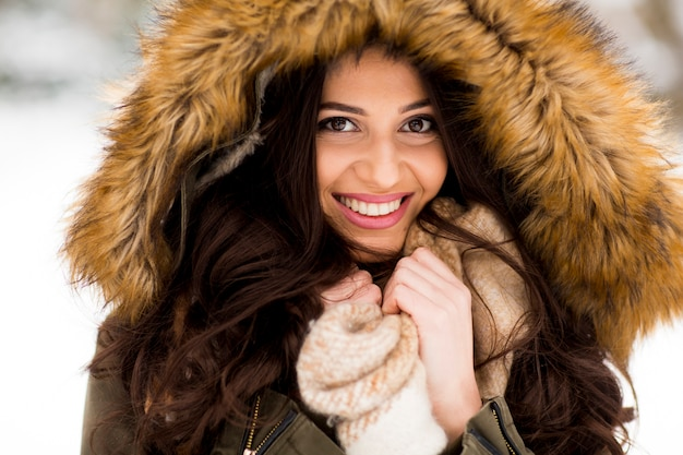Young woman with a fur hood in the park on the snow