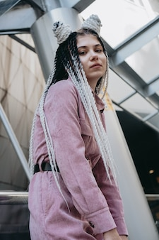 Young woman with futuristic looks girl with black and white dreadlocks or pigtails against the background of a futuristic building