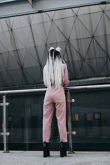 Young woman with futuristic looks girl with black and white pigtails standing with her back against the background of a futuristic building