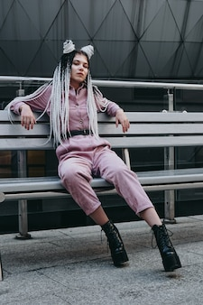 Young woman with futuristic looks sitting on a bench girl with black and white pigtails against the background of a futuristic building