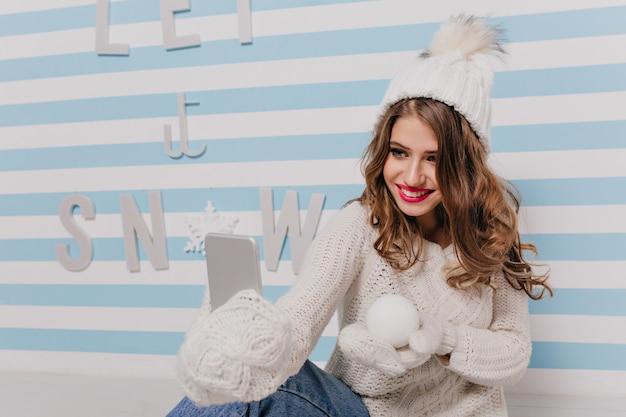 Giovane donna con un sorriso gentile e gli occhi azzurri posa per selfie, mostrando la palla di neve in mano. ritratto dell'interno della ragazza in vestiti bianchi lavorati a maglia