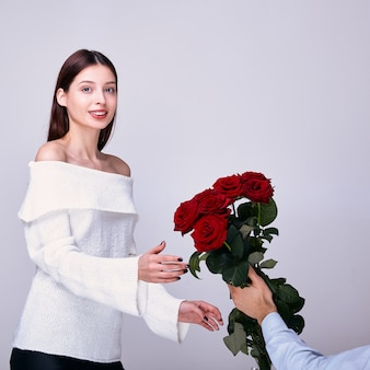 A young woman with a gentle smile receives red roses.