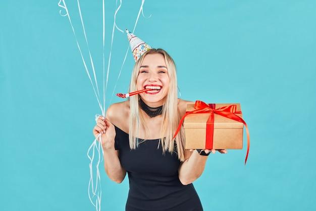 파란색 벽에 생일을 축하하는 동안 선물 상자와 baloons 및 불고 파티 경적 또는 소음기를 가진 젊은 여자