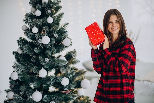 クリスマスツリーのそばにギフトボックスを持つ若い女性
