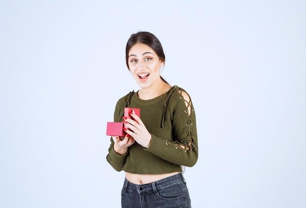 Молодая женщина с подарочной коробкой, чувствуя себя счастливой на белом фоне.