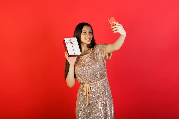 그녀의 전화에 selfie를 만드는 선물 상자와 젊은 여자