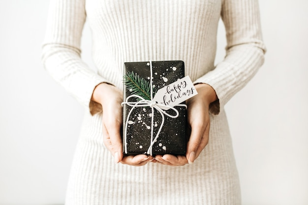 Young woman with gift box with tag happy holidays on white surface.