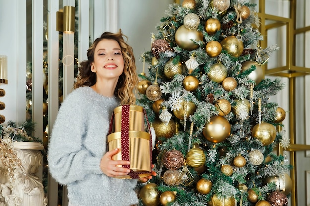 Young woman with gift standing at christmas tree happy and looking camera. white silver color on background of living room and fireplace on merry christmas and happy new year. atmospheric moments