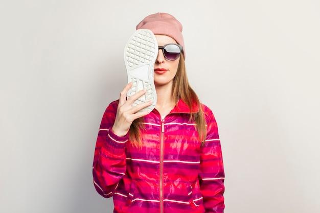 Молодая женщина в очках, шляпе и розовой спортивной куртке с серьезным лицом закрывает лицо одной кроссовкой