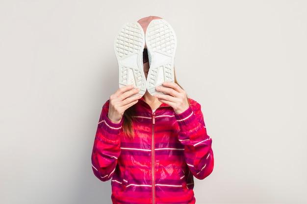 Молодая женщина в очках, шляпе и розовой спортивной куртке с серьезным лицом закрывает лицо кроссовками