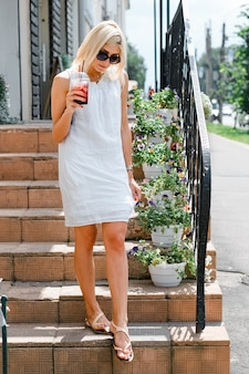フレッシュジュースを保持し、外の階段に立っている眼鏡をかけて若い女性。白いリボンのドレスのブロンドの女の子