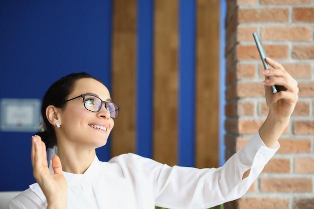 Молодая женщина в очках держит мобильный телефон и машет рукой