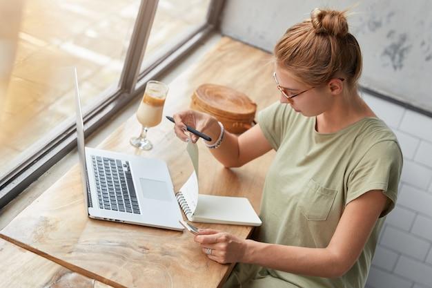 カフェで眼鏡を持つ若い女性