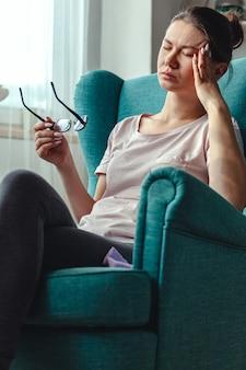 Молодая женщина с очками в руках сидит в кресле и страдает от