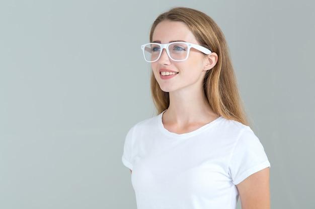 Молодая женщина в очках, изолированных на сером