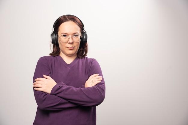 Giovane donna con gli occhiali ascoltando musica in cuffia su uno sfondo bianco. foto di alta qualità