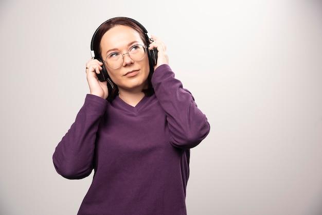 Молодая женщина в очках, слушая музыку в наушниках на белом. фото высокого качества