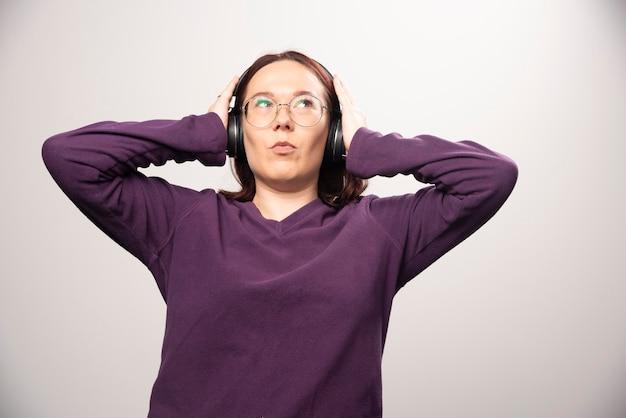 白のヘッドフォンで音楽を聴いている眼鏡をかけた若い女性。高品質の写真