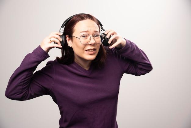 안경 흰색에 헤드폰에서 음악을 듣고 젊은 여자. 고품질 사진