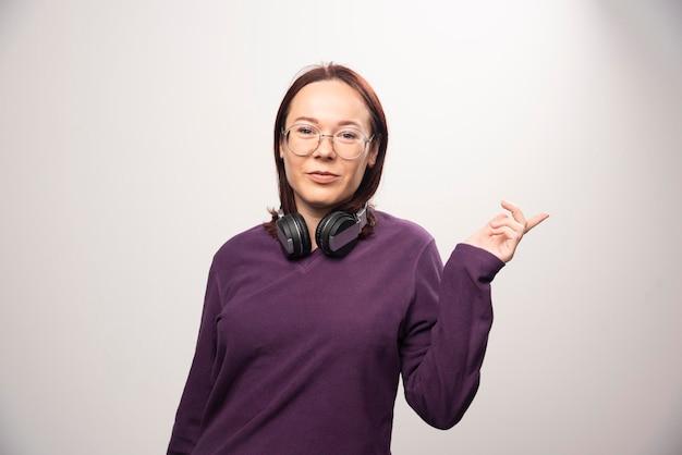 흰색에 헤드폰에서 포즈 안경 젊은 여자. 고품질 사진