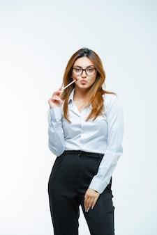 뺨에 펜을 누르는 안경을 쓴 젊은 여성