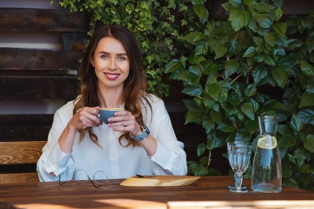 眼鏡をかけた若い女性がカフェのテーブルに座っています