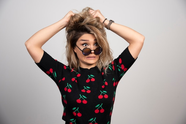 Giovane donna con gli occhiali in piedi sul muro grigio.