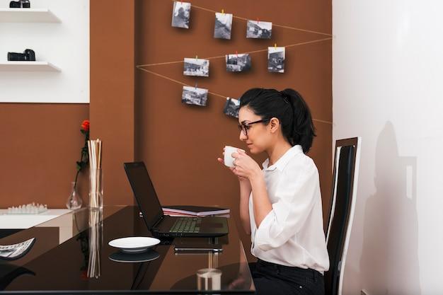 Молодая женщина в очках, принимая перерыв на кофе во время работы в ее временном домашнем офисе