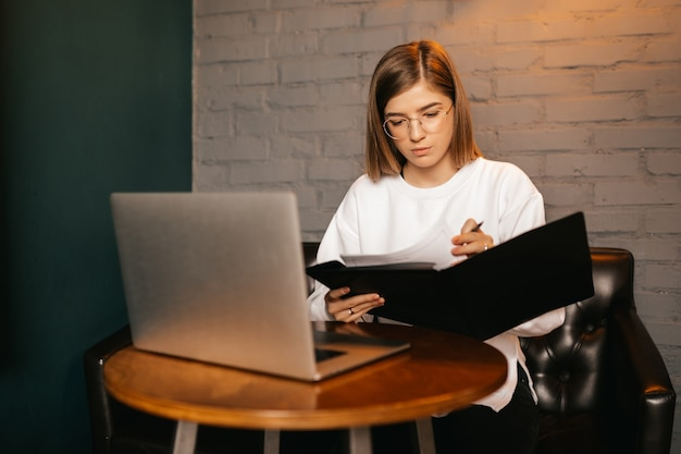 Young woman with glasses writing and using laptop at cafe bar