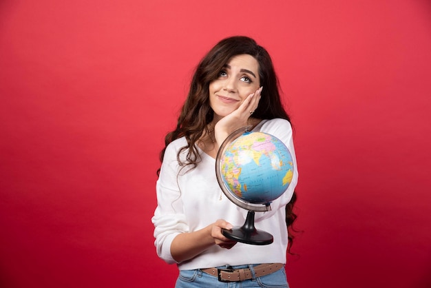 Young woman with globe dreaming about travel on red background. high quality photo