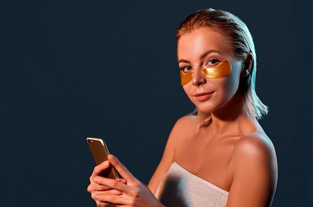Young woman with gold eyes patches and phone in hand