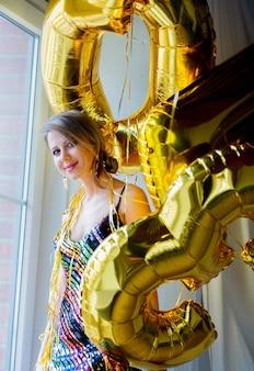 窓の近くの黄金の風船を持つ若い女性。人はヴィンテージの80ドレスと髪型です。家に