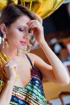 30歳の誕生日に金色の風船を持つ若い女性。人はヴィンテージの80ドレスと髪型です。家に