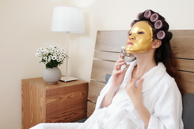 Young woman with golden rejuvenating face mask on massaging face with roller, spa day at home concept