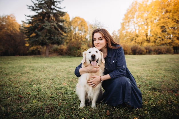 Young woman with a golden retriever in a beautiful autumn park