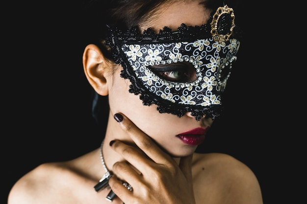 Young woman with a gray venetian mask