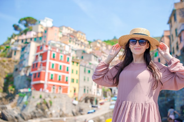 Young woman with great view at old village riomaggiore, cinque terre, liguria