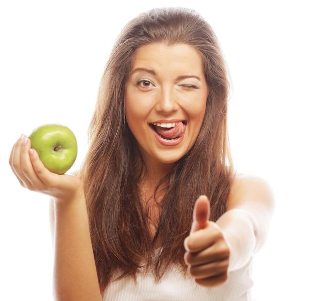 Молодая женщина с зеленым яблоком и показывает палец вверх