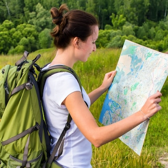 Young woman with green backpack reading map on hiking trip outdoors