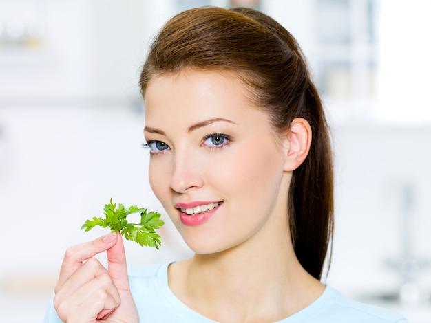 手に緑のフェンネルを持つ若い女性-キッチンで