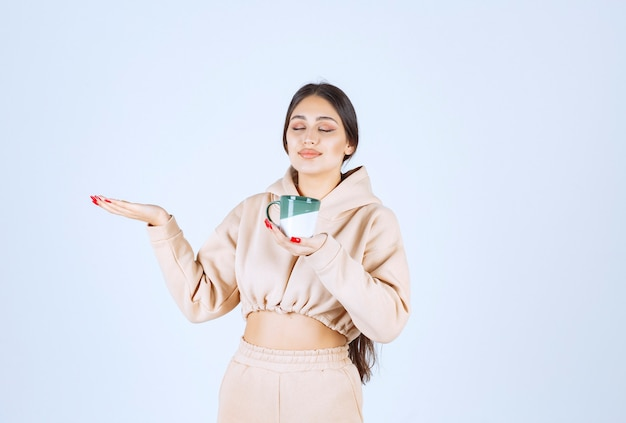 Young woman with a green mug pointing at somewhere on the left